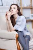 Uma morena nova flirty atrativa está sentando-se em uma grande cadeira macia Fotos de Stock