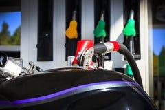 Uma motocicleta escura No tanque uma arma para abastecer-se Profundidade rasa do corte imagens de stock royalty free