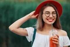 Uma mulher à moda nova que tem uma bebida de refrescamento ao andar imagens de stock royalty free