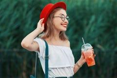 Uma mulher à moda nova que tem uma bebida de refrescamento ao andar fotografia de stock