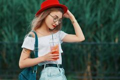 Uma mulher à moda nova que tem uma bebida de refrescamento ao andar fotos de stock royalty free