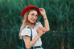 Uma mulher à moda nova que tem uma bebida de refrescamento ao andar fotos de stock