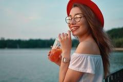 Uma mulher à moda nova que tem uma bebida de refrescamento ao andar fotografia de stock royalty free
