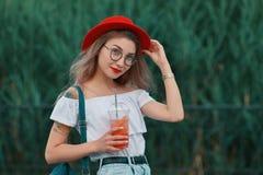 Uma mulher à moda nova que tem uma bebida de refrescamento ao andar foto de stock royalty free