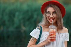 Uma mulher à moda nova que tem uma bebida de refrescamento ao andar foto de stock