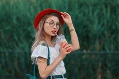 Uma mulher à moda nova que tem uma bebida de refrescamento ao andar imagem de stock