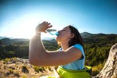 Uma mulher é água bebendo isolada no branco imagem de stock royalty free