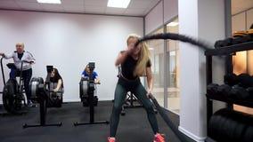 Uma mulher é contratada ativamente em exercícios do gym com cordas do combate durante o treinamento do intervalo da alta intensid vídeos de arquivo