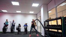 Uma mulher é contratada ativamente em exercícios do gym com cordas do combate durante o treinamento do intervalo da alta intensid filme