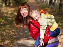 Uma mulher é terra arrendada sua criança nela para trás imagens de stock