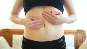 Uma mulher é um estômago gordo Conceito da perda do excesso de peso e de peso Uma menina em um maiô puxa a pele em seu estômago filme