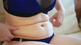 Uma mulher é um estômago gordo Conceito da perda do excesso de peso e de peso Uma menina em um maiô puxa a pele em seu estômago vídeos de arquivo