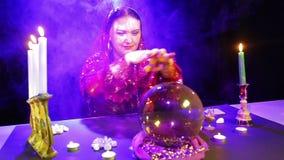 Uma mulher aciganada em um vestido vermelho em uma sala para a fortuna que diz nos sopros de fumo l? o futuro em uma bola do espe video estoque