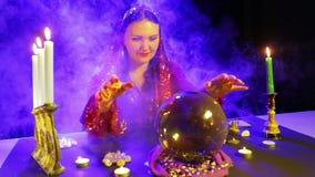 Uma mulher aciganada em um vestido vermelho em uma sala para a fortuna que diz nos sopros de fumo l? o futuro em uma bola do espe filme