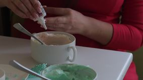 Uma mulher adiciona uma gota da coloração de alimento de um tubo do queijo creme Creme colorindo para a lubrificação do bolo vídeos de arquivo