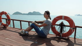 Uma mulher admira as vistas bonitas da baía longa do Ha filme