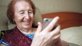 Uma mulher adulta escreve uma mensagem e olhares nas fotos em seu smartphone novo Avó com enrugamentos profundos dentro feliz