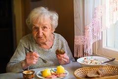 Uma mulher adulta está tendo o jantar que senta-se em uma tabela em sua casa fotografia de stock