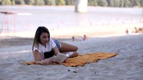 Uma mulher adulta nova que coloca na cobertura, lendo um livro roupa ocasional, verão na praia grupo de pessoas fora de foco, filme