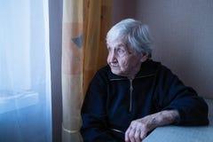 Uma mulher adulta olha longingly para fora a janela de sua casa imagem de stock
