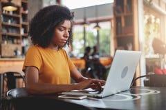 Uma mulher africana que usa o portátil na cafetaria fotografia de stock royalty free