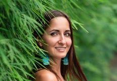 Uma mulher agradável da nacionalidade caucasiano com um sorriso inclinado contra a cerca verde, close-up imagens de stock royalty free