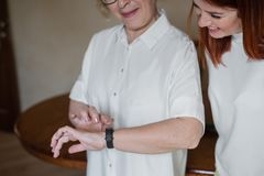 Uma mulher ajuda uma m?e mais idosa a p?r sobre um bracelete da aptid?o Uma filha adulta ajuda sua m?e a classificar para fora o  fotografia de stock