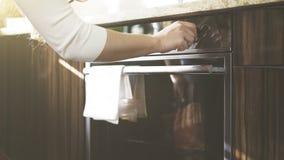 Uma mulher ajusta a temperatura no forno da cozinha Foto de Stock Royalty Free