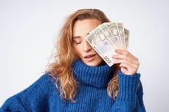 Uma mulher alegre em uma camiseta, peça das tampas da cara com mone Fotos de Stock Royalty Free