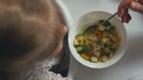 Uma mulher alimenta uma menina de uma colher com sopa vegetal vídeos de arquivo