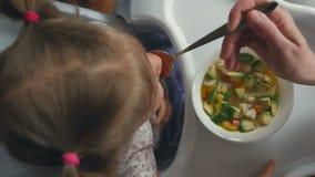 Uma mulher alimenta uma menina de uma colher com sopa vegetal video estoque