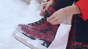 Uma mulher amarrou acima seus laços em sapatas vermelhas brilhantes da patinagem no gelo fotografia de stock