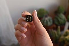 Uma mulher anônima que guarda um cubo preto com pontos dourados foto de stock royalty free