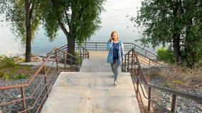 Uma mulher anda acima das escadas do banco de rio vídeos de arquivo