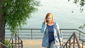 Uma mulher anda acima das escadas do banco de rio video estoque