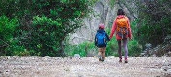 Uma mulher anda com seu filho atrav?s da floresta fotos de stock