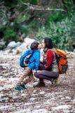 Uma mulher anda com seu filho atrav?s da floresta imagens de stock