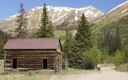 Uma mulher anda por uma cabine velha no laço alpino Backcountry Byw foto de stock
