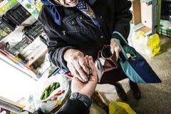 Uma mulher aposentada idosa dá-lhe o último dinheiro em uma loja imagens de stock