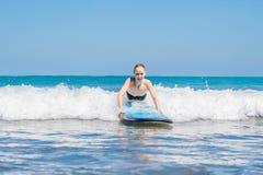 Uma mulher aprende surfar na espuma Bali Indonésia fotos de stock royalty free