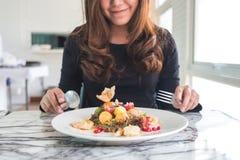 Uma mulher asiática bonita aprecia comer a salada de frutos fotografia de stock royalty free