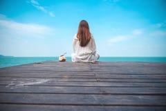 Uma mulher asiática bonita no vestido branco que senta e que olha o mar e o céu azul no balcão de madeira imagem de stock royalty free