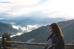 Uma mulher asiática bonita que está sozinha e que olha montanhas no dia nevoento com fundo do céu azul imagens de stock