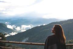 Uma mulher asiática bonita que está sozinha e que olha montanhas no dia nevoento com fundo do céu azul imagem de stock