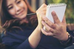 Uma mulher asiática bonita que guarda o lápis preto e que escreve no caderno que senta-se no café moderno com o jardim do vertica Imagens de Stock Royalty Free