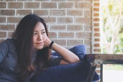 Uma mulher asiática bonita senta-se com o queixo que descansa em suas mãos acima de um descanso azul com sentimento feliz e relax Fotografia de Stock