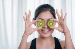 Uma mulher asiática está guardando o fruto de quivi e está apreciando cuidados médicos foto de stock royalty free