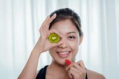 Uma mulher asiática está guardando o fruto e a morango de quivi com h feliz foto de stock