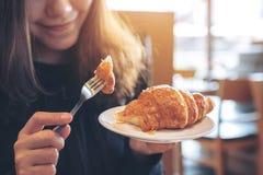 Uma mulher asiática que guarda e que come uma parte de croissant fotografia de stock royalty free
