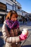 Uma mulher asiática que guarda o copo do chá na rua foto de stock
